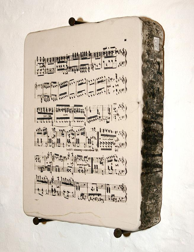 A lithographic stone for printing music. The music is written backwards on the stone.
